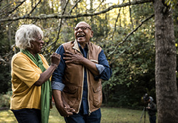 Image of senior couple laughing on a walk in nature