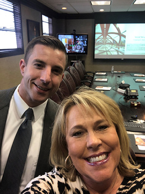 Dave Ghormley and Teia Sebre taking selfie in conference room